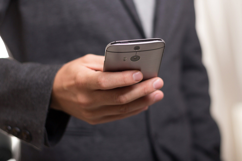 extorsión telefónica un hombre consulta su teléfono móvil