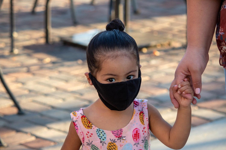 Mascarillas para niños. Una niña con mascarilla acompaña a su madre