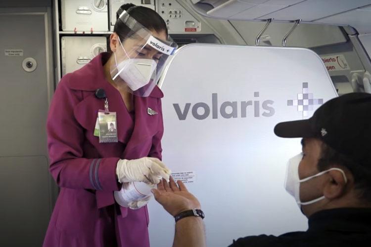 bioseguridad: una azafata de Volaris aplica gel antibacterial en la mano del pasajero de un avión