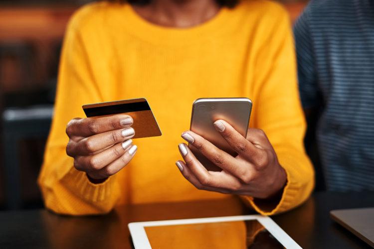 ciberseguridad una mujer consulta un smartphone y su tarjeta bancaria