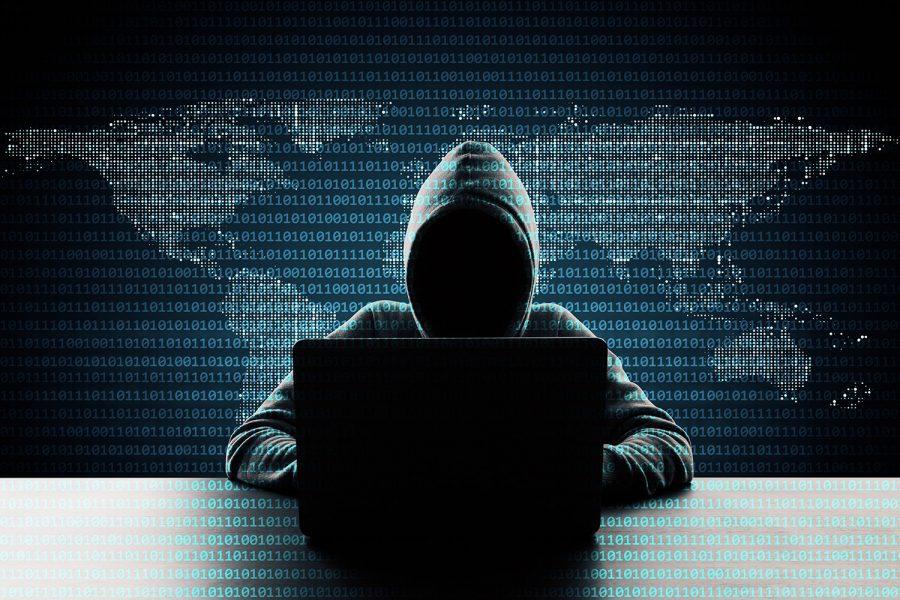 Hacker informático encapuchado con ordenador portátil