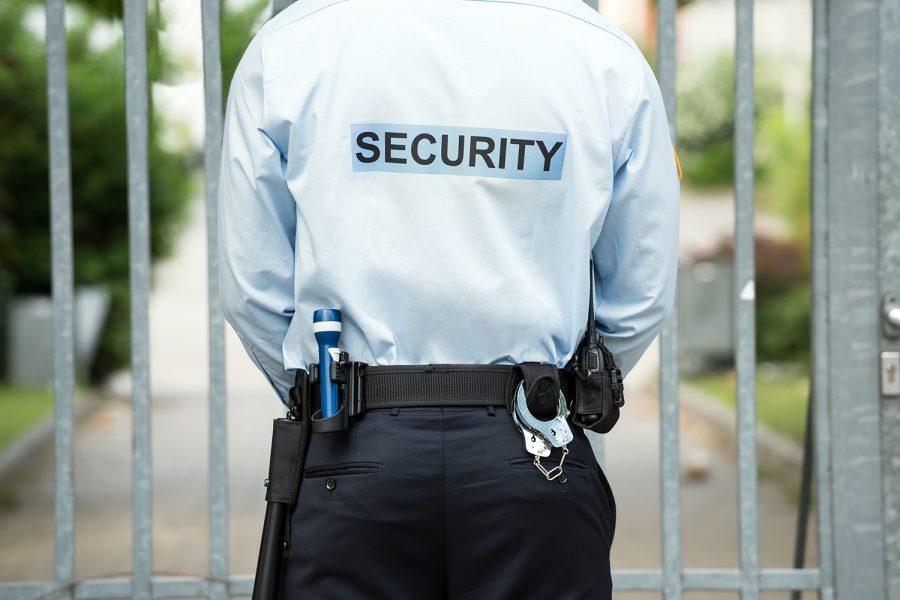 un vigilante de seguridad privada ante una puerta de rejas