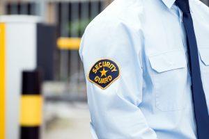 un guarda de seguridad privada junto a un control de accesos