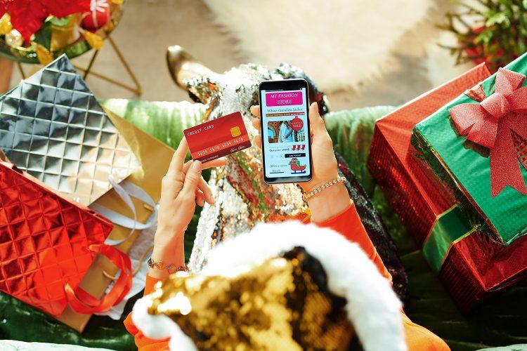 una mujer realiza compras en línea con su smartphone en Navidad
