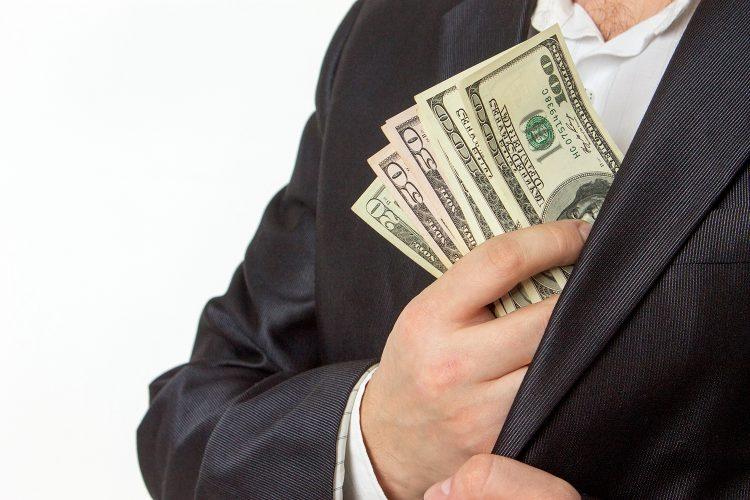 un hombre guarda dólares en su americana