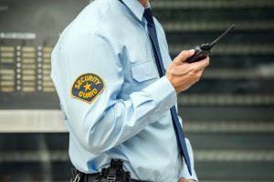un guardia de vigilancia y seguridad privada comunicándose a través de su radio