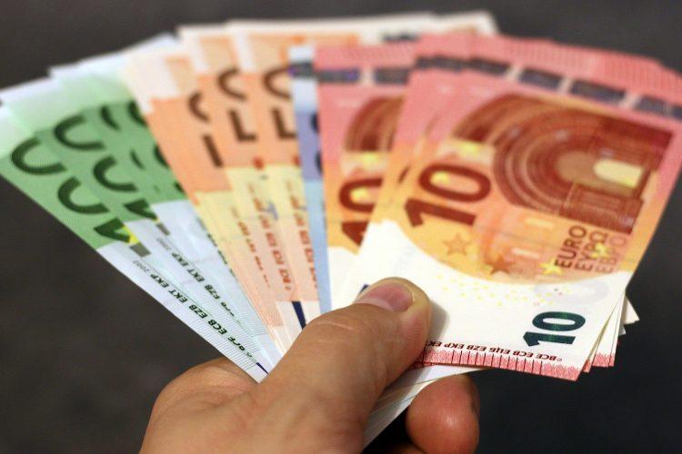 un hombre sostiene billetes de euro en su mano