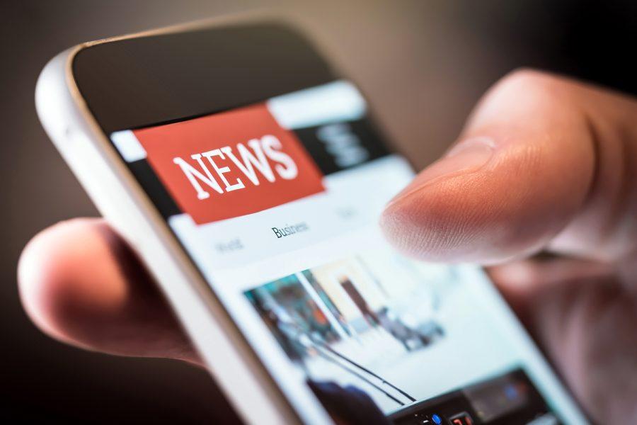un hombre lee las noticias en su smartphone