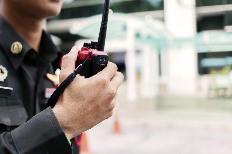 Un vigilante de seguridad privada presta servicio con su radio