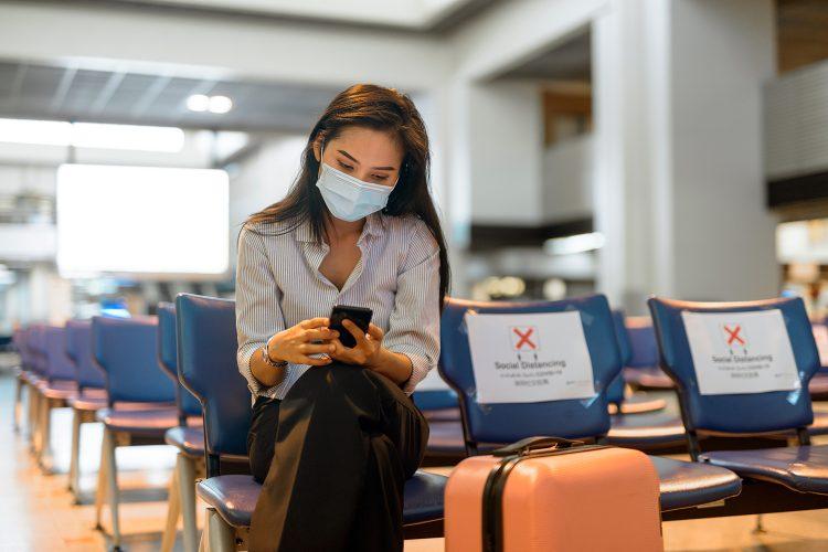 una mujer utiliza su smartphone en un aeropuerto