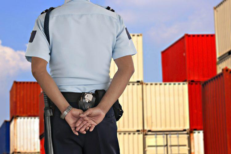 un guardia de seguridad privada vigila un centro logístico de contenedores