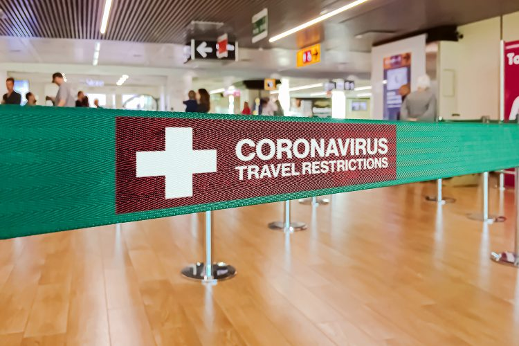 señal de restricciones por coronavirus en un aeropuerto