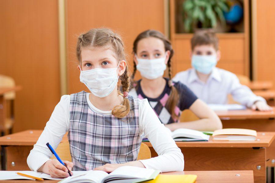 niños con mascarilla estudian ciberseguridad en un colegio