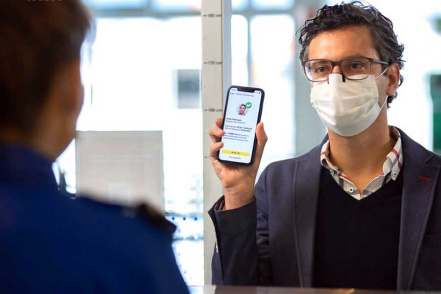 un pasajero de avión enseña su smartphone con la aplicación IATA Travel Pass