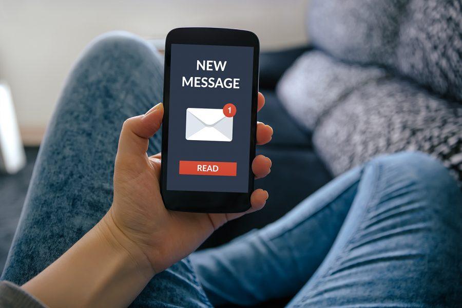 un hombre recibe un SMS en su smartphone