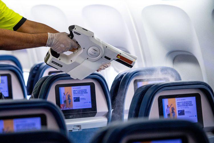 un operario de limpieza desinfecta la cabina de un avión comercial
