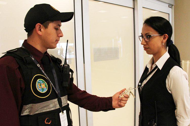 Un guardia de seguridad comprueba la credencial de una empleada en un aeropuerto ecuatoriano