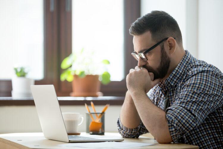 un hombre mira su ordenador con preocupación