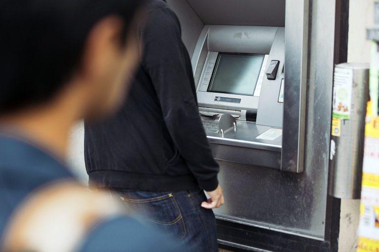 una persona vigila al usuario de un cajero automático