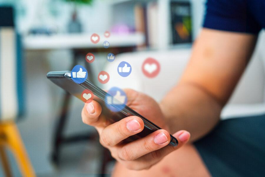un joven hace uso de las redes sociales en su smartphone