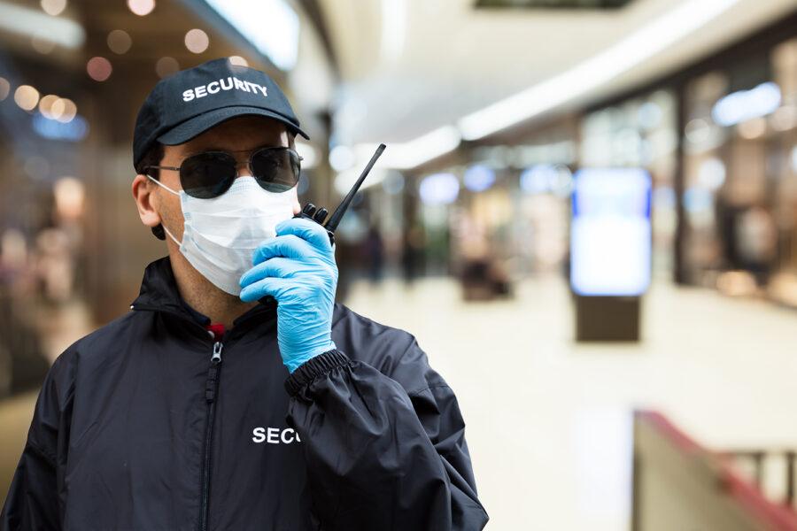un guarda de seguridad privada se comunica por radio en un centro comercial