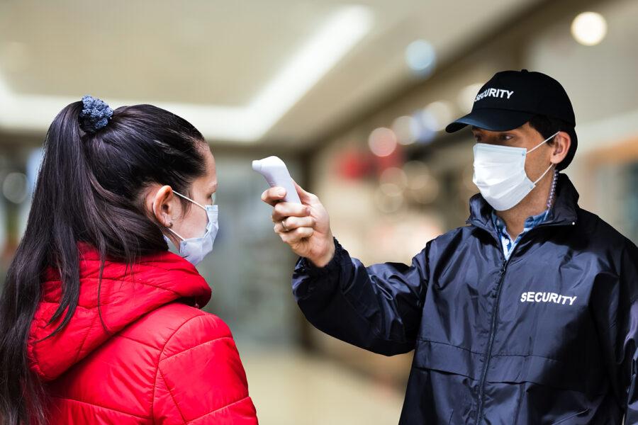 un guardia de seguridad privada toma la temperatura corporal a una cliente de un centro comercial
